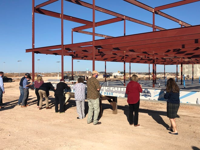Canyon ISD officials, Canyon ISD board members and community members sign the structural beam at the West Plains High School site before it is placed Thursday afternoon.