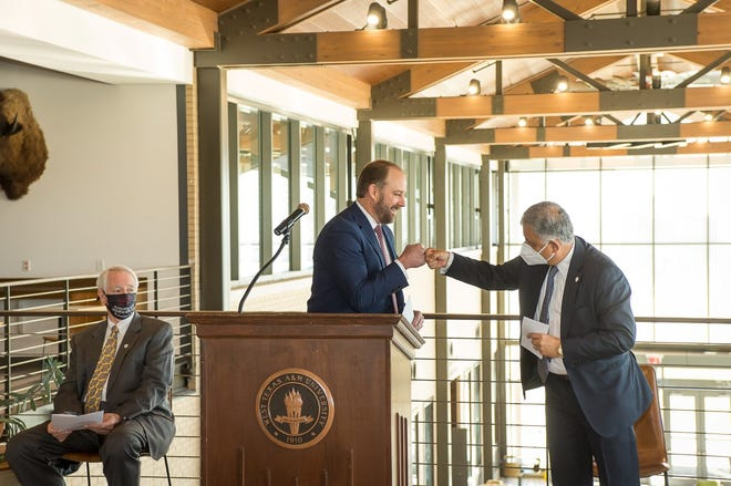 Amjad Abdullat, the dean of the West Texas A&M University's College of Business, gives a fist bump to David Terry, the chief executive officer of the Engler Foundation, after receiving the check from the foundation. [Photos by Shaie Williams / For the Amarillo Globe-News]