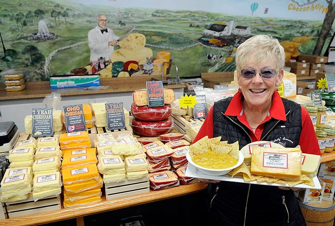 Ronda Poorbaugh poses with a tray of cheese and cheese dip at Grandpa's Cheesebarn, which is owned by her family in Ashland. TOM E. PUSKAR/TIMES-GAZETT