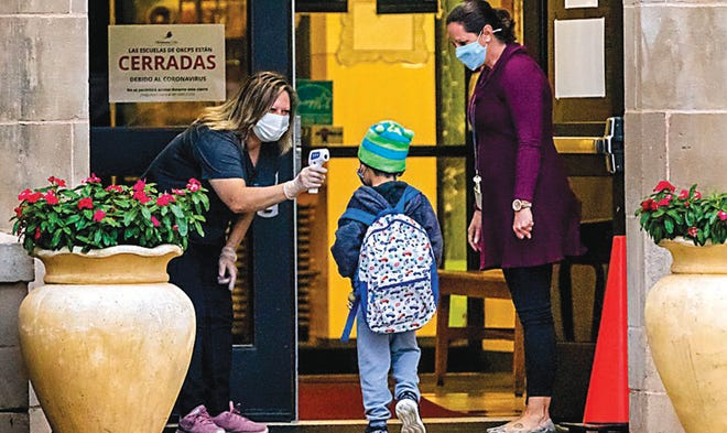 Hawthorne Elementary principal Melinda Elms, right, looks on as a student has their temperature taken as Pre-K and kindergarten students arrive for the first day of in person class at Hawthorne Elementary in Oklahoma City, Okla. on Tuesday, Oct. 20, 2020.