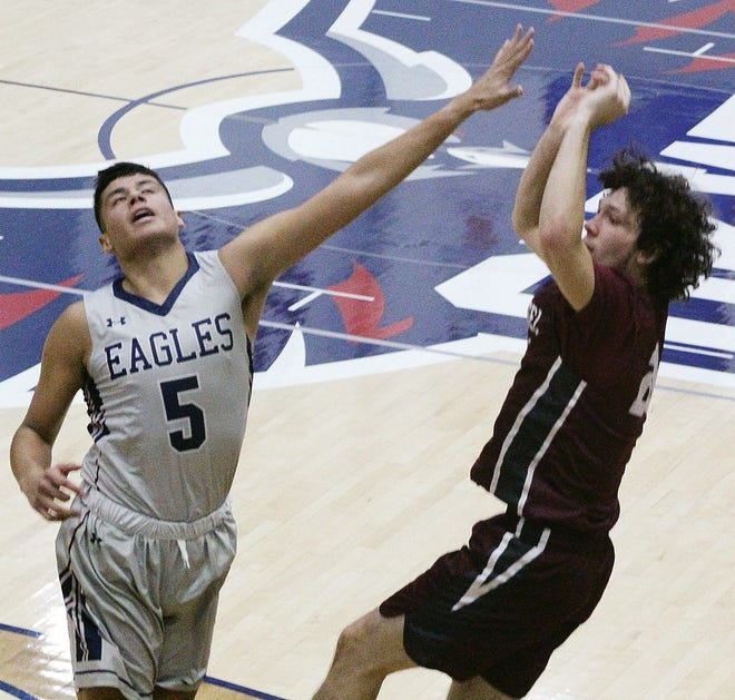 Oklahoma Wesleyan University's Del Jelley, left, puts maximum pressure on a shot by an Evangel player during men's hoop action late last month.