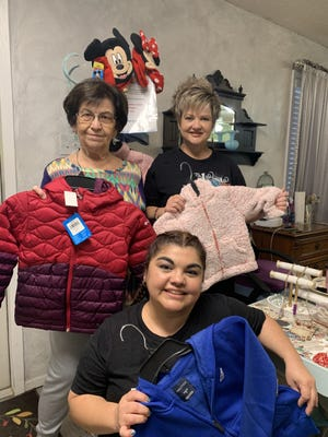 Leslie Reedy, DelainaEsparza, and Kim Sliger show off some of the winter clothing donated by friends and clients of Hometown Spa and Salon for foster children of Brown County. The drive continues until November 15. New winter clothing may be taken to 2909 Coggin Ave.