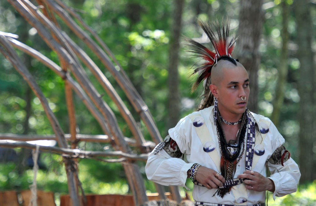 Phillip Wynne adjusts his outfit next to a wetu before the grand entry at the annual Mashpee Wampanoag Powwow in 2011.