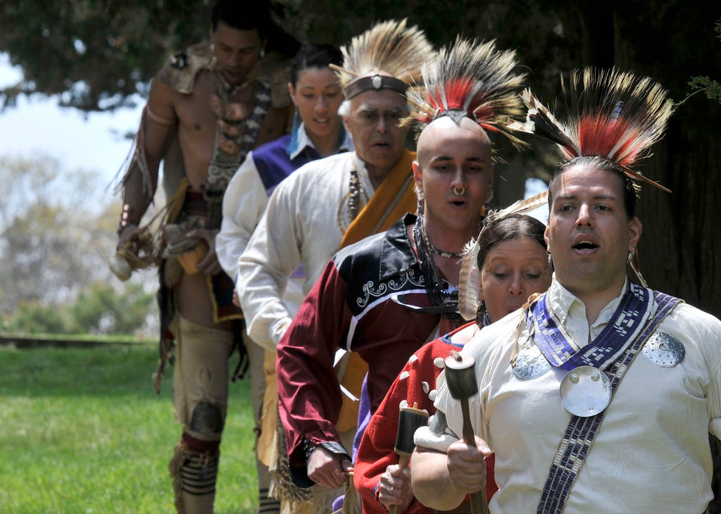 Jonathan Perry, right, a member of the Wampanoag Tribe of Gay Head (Aquinnah), leads a group of native dancers onto the stage at the Cape Cod National Seashore's Salt Pond Visitor Center in 2011 during a celebration of the tribe.