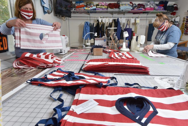 Beth Bourque, left, and Lynn Lizak-Mercier work their way through piles of flags they are finishing up at Lynn's Alterations and Sew-On shop in Orleans. The flags were created to remember those whose lives have been lost or changed by COVID-19. [Steve Heaslip/Cape Cod Times]