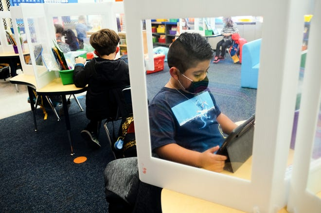 Kindergartner Yahir, 5, right, sets up a lesson on his iPad while surrounded by a barrier as part of COVID-19 precautions in classrooms on Monday, Nov. 2, 2020 in Hilliard, Ohio.