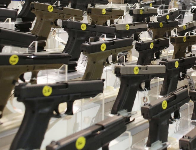 A customer looks at a pistol at a vendor's display at a gun show held by Florida Gun Shows in Miami on Saturday, Jan. 9, 2016. The cities of Columbus and Dayton are suing the Ohio Attorney General's office over what they say is a failure to keep state background check systems updated with information about felony convictions.