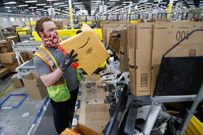 Ethan Kuespert of Canal Winchester packages customer orders this month at the Amazon distribution center in Etna Township.