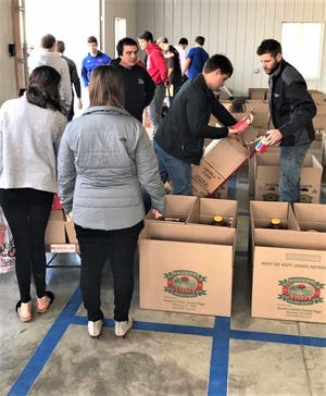 Share-A-Christmas volunteers prepare boxes of food and gifts for delivery from the Baker Building at Harvest Ridge.