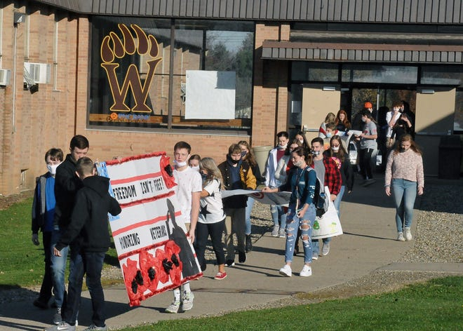 John R. Lea Middle School students proceed to the Patriots Parade route Friday morning when the school held its annual veteran recognition ahead of Veterans Day. MIKE SCHENK PHOTO, THE DAILY RECORD
