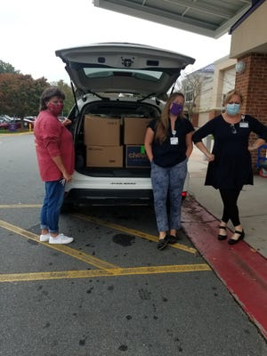 Martha Haynes (from left) of Crisis Ministry of Davidson County, accepts boxloads of toiletry kits from Payton Williams and Kristen Fulp with Novant Health Thomasville Medical Center. Novant Health employees made 3,000 kits to disperse to several nonprofits in the Triad as part of the United Way Day of Caring campaign.