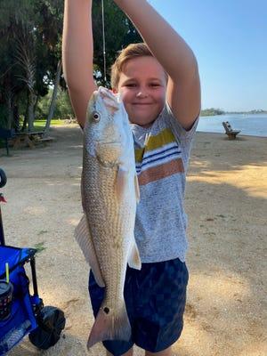 Luke Thomas holds a large redfish.