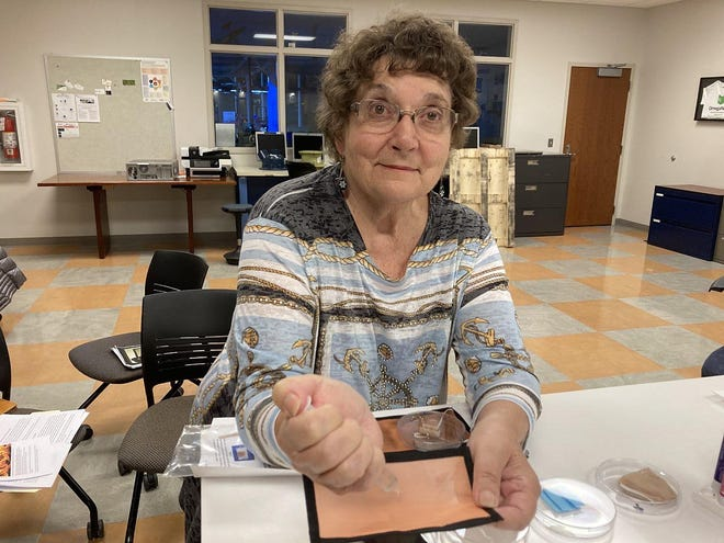 Phyllis Kuhn, a longtime Erie researcher, shows how a copper-mesh face mask she helped design prevents fluid from seeping through. Kuhn, shown at Penn State Behrend on Nov. 5, is selling the face masks through her business, Kuhn Copper Solutions.