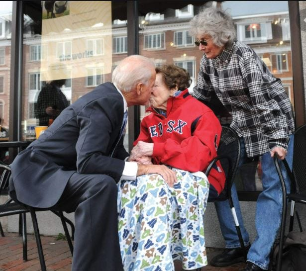 President-Elect Joe Biden gives a kiss to former Mayor Eileen Foley in 2012 as her daughter Mary Carey Foley visits too during a stop in downtown Portsmouth.