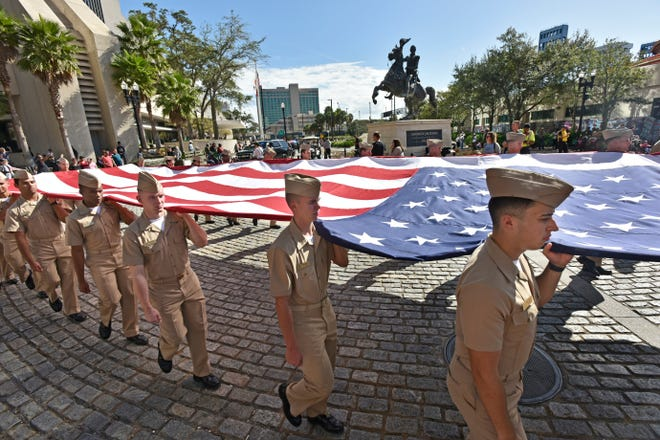 Members of the Jacksonville University Navy ROTC carry the U.S. flag during the city's 2019 Veterans Day Parade downtown.