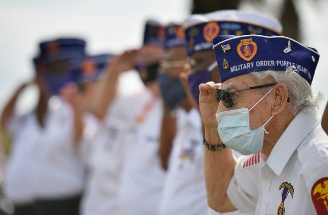 World War II Navy veteran Frank Purpura salutes with other Purple Heart recipients during a Veterans Memorial relocation and Purple Heart ceremony Friday at Oceanfront Park in Jacksonville Beach.
