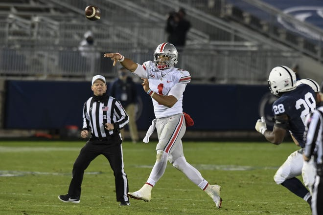 Ohio State quarterback Justin Fields (1) passes while being chased by Penn State defensive end Jayson Oweh (28) in the fourth quarter of an NCAA college football game in State College, Pa., Saturday, Oct. 31, 2020. Ohio State won 38-25. (AP Photo/Barry Reeger)