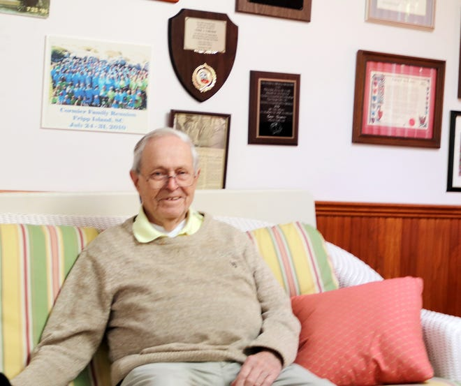 Veteran TGN correspondent Omer Cormier, 90, sitting in the den of his Chestnut Street home. The den walls are adorned with many plaques, celebrating and honoring his newspaper career over the years.