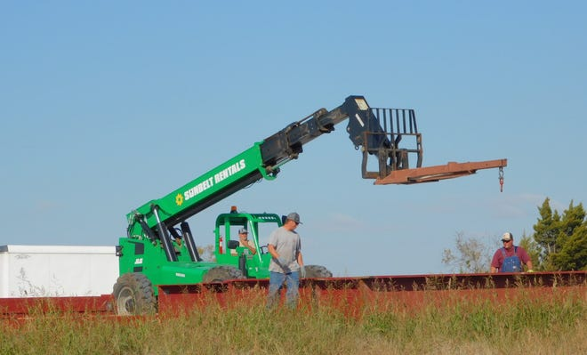 Crews work to move metal beams at the site of a proposed hotel along Loy Lake Road Friday.