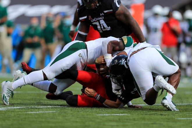 South Florida linebacker Antonio Grier, left, sacks Cincinnati's Desmond Ridder with support from Devin Gil, right, on Oct. 3.