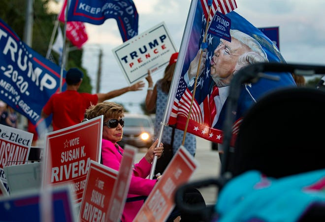 A Trump supporter surrounded by Trump campaign signs works a polling site on Election Day at the Wellington branch of the county library system.