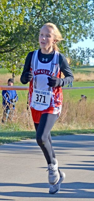 Macksville Mustang Madison Butler (371) charges to the finish line in the 1A state cross country championship at Wamego Country Club.