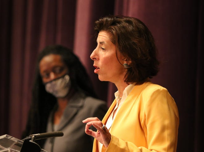 Dr. Nicole Alexander-Scott listens at back as Gov. Gina Raimondo speaks during her weekly cover virus update at the Veterans Memorial Auditorium on Thursday.