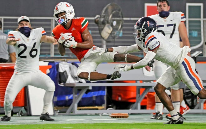 Miami wide receiver Mark Pope catches a first-half pass against Virginia's Nick Grant (1) during their Oct. 24 game in Miami Gardens, Fla. Miami plays at North Carolina State on Friday.