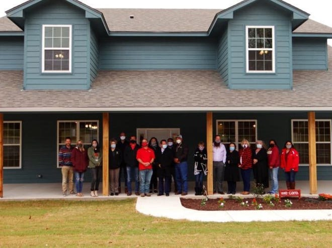 Leadership from Community Renewal of Pottawatomie County and the Absentee Shawnee Housing Authority stand in front of their new Friendship House just before taking the first tour of the new facility.