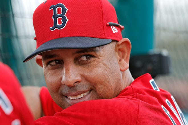Boston Red Sox manager Alex Cora smiles from behind the batting cage during spring training in 2019. The Red Sox rehired Cora as manager last week less than a year after letting him go because of his role in the Houston Astros cheating scandal.