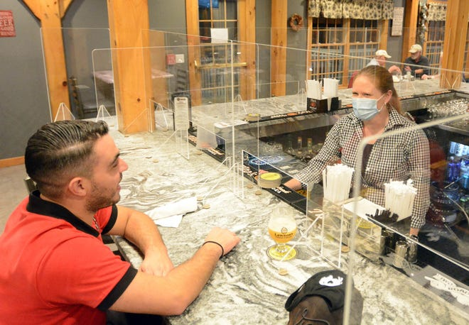 Mike Lydle of Taftville talks with bartender Jessica Salisbury as he waits for his dinner and a beer Thursday at Tulli's Tap House at River Ridge Golf Course in Griswold. [John Shishmanian/ NorwichBulletin.com]