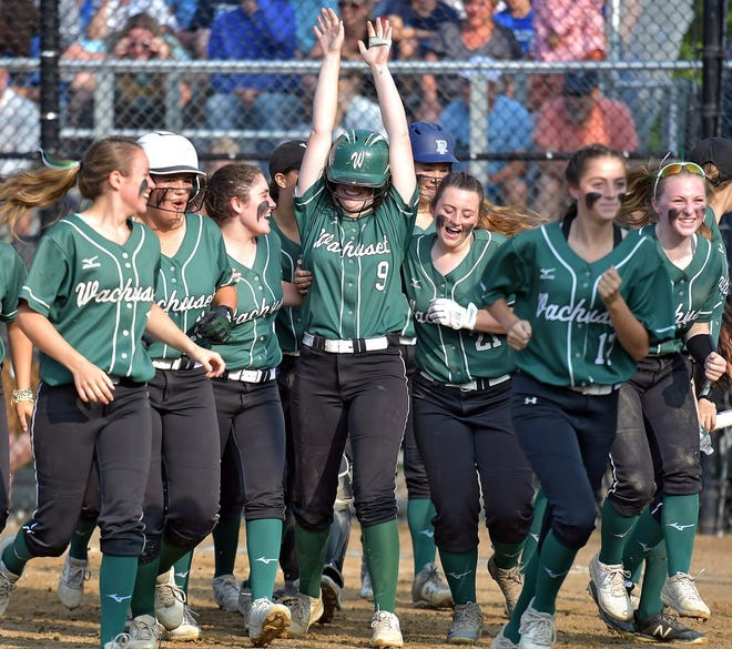 Wachusett's Abbygail Simes raises her arms as she is congratulated by teammates after blasting a game-tying home run in the sixth inning of the 2019 Division 1 state softball final.