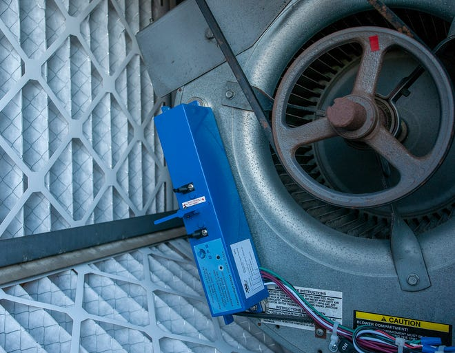 An ionization unit is installed on a blower motor, next to the air filters. inside the ventilation system of Worcester Technical High School Friday.