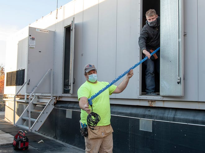Workers from Automated Building Systems install an ionization unit into the ventilation system on the roof of Worcester Technical High School Friday. The systems are being install in Worcester schools to help protect against the spread of coronavirus.