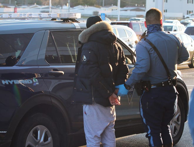 State police arrest a man outside the Price Chopper on Greenwood Street on Wednesday in Worcester. The man was one of three involved in a high-speed chase in a stolen car on the Mass Pike.
