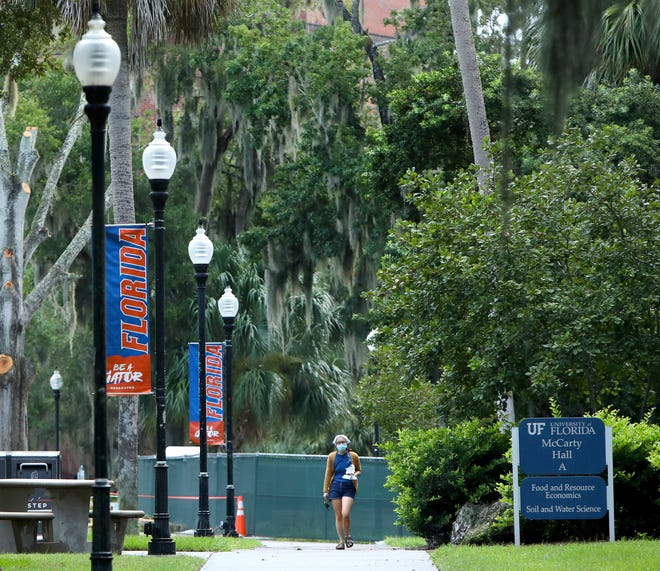 A student walks along a sidewalk at the University of Florida as the first day of classes begin at the school, in Gainesville Fla. Aug. 31, 2020.