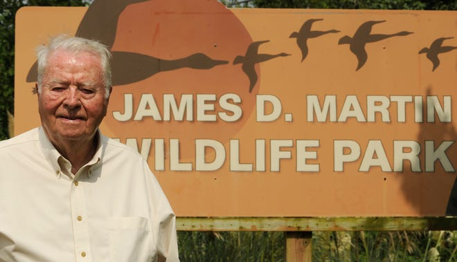 James D. Martin is shown in a 2011 photo in front of the sign at the wildlife refuge in Gadsden that bears his name.