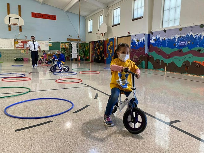 Ahtziri Fuentes, a kindergartner at Parkview Elementary School, rides one of the brand new bicycles donated to the school by Pueblo Police officers.