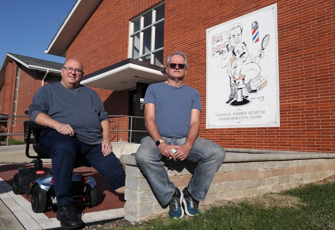 Mike Ippoliti (left), director and curator of the National Barber Museum and Hall of Fame, and artist David Walker are shown at the museum's memorial patio Nov. 6 after Walker's mural depicting Ippoliti getting a haircut from museum founder Ed Jeffers was installed.