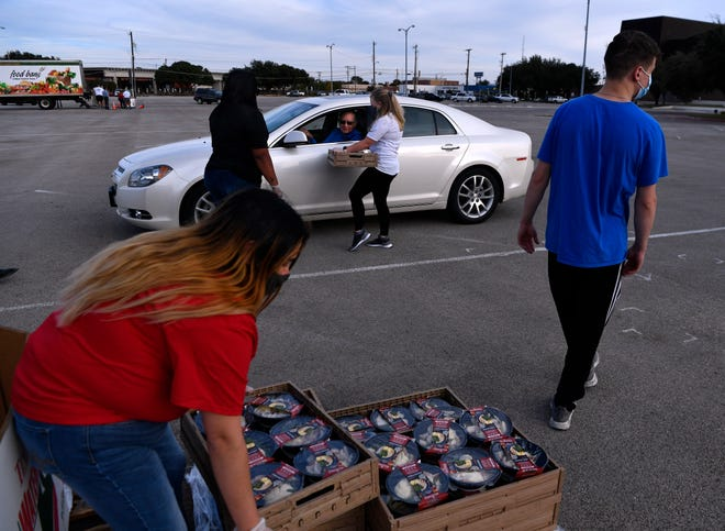 Katelyn Slaughter lifts a pallet of holiday meals as more cars pull up for the Feast of Sharing drive-thru meal at the Abilene Convention Center on Wednesday. H-E-B and Food Bank of West Central Texas have split the annual meal into a two-day event, the second being Dec. 17.