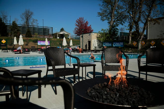 Gisela Diercks, of Hyde Park, swims laps in the outdoor pool as the fire pit space remains empty at the Cincinnati Sports Club in Fairfax, Ohio, on Friday, Nov. 6, 2020. With a weekend weather forecast calling for daytime temperatures in the 70s, the club has decided to keep its outdoor pool open for members to enjoy a few more days of poolside sunshine.