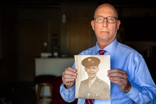 Ira Naiditch holds a photo of his father, Sanford Naiditch, at his home in Ankeny on Nov. 5, 2020. Sanford Naiditich served in the Army's 517th field artillery in World War II.