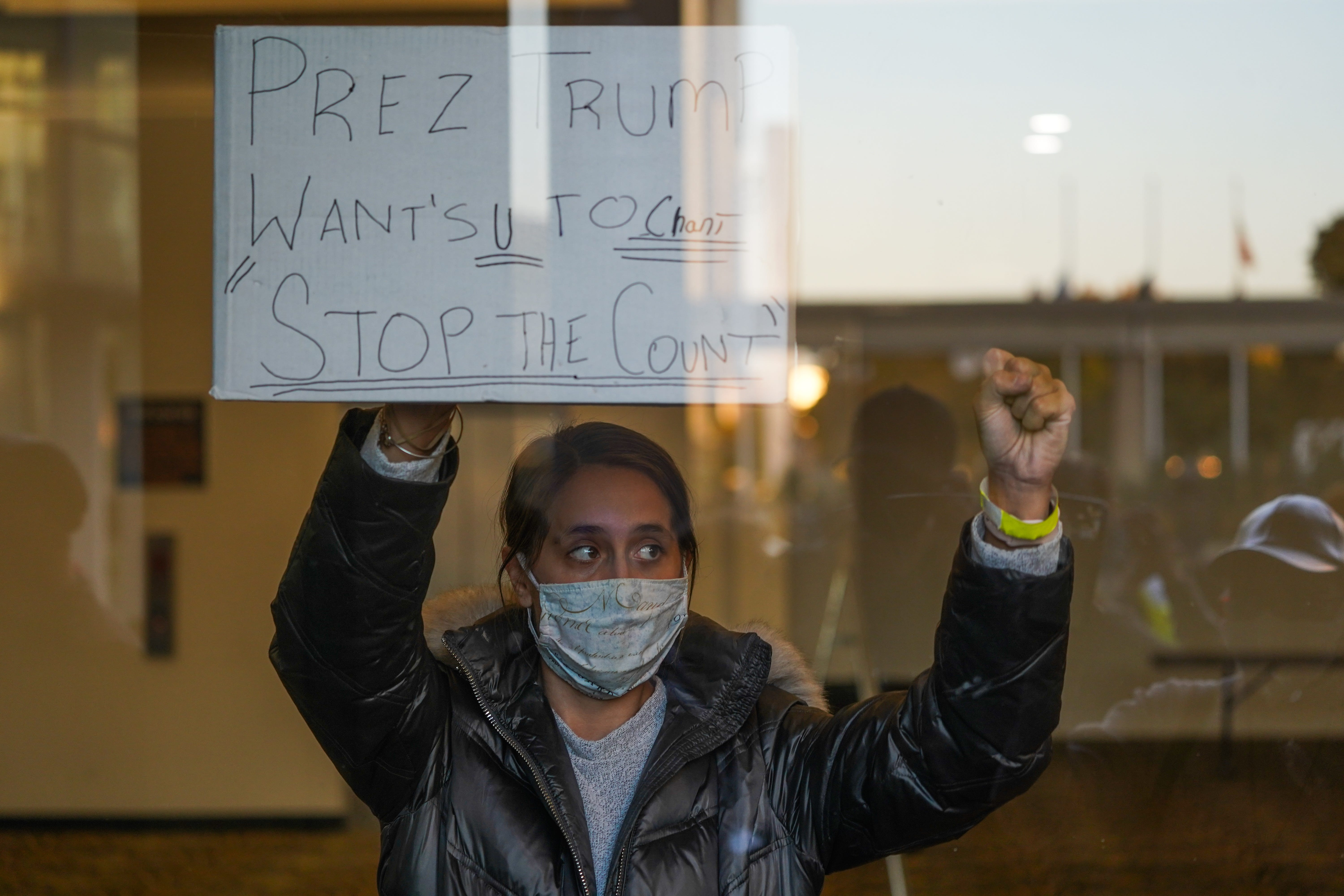 """A woman with the Trump campaign holds a sign to get Republican challengers outside the TCF Center to chant, """"Stop the count!"""" as absentee ballots were counted in Detroit on Wednesday, Nov. 4, 2020."""