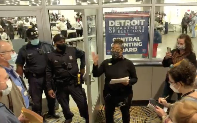 Election worker Sommer Woods speaks to challengers gathered at an entrance to TCF during vote counting in Detroit.
