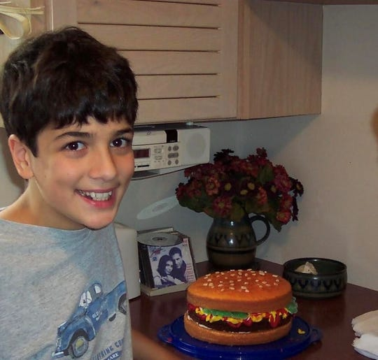 Jonny Manganello as a child in Grosse Pointe with his first cake, which he designed to resemble a cheeseburger.