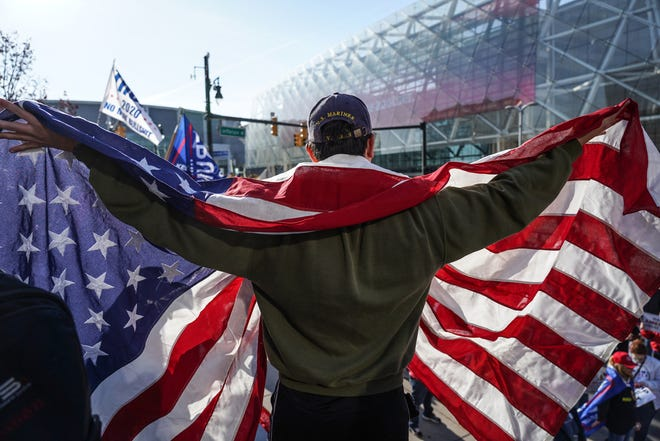 Michael Foy of Wixom holds his flag open while standing above the crowd gathered for a rally in support of President Trump outside of the TCF Center in Detroit on Friday, Nov 6, 2020 where the absentee ballot count for the city of Detroit took place. Trump supporters gathered to express their concern for the results after Democratic Presidential Candidate Joe Biden won the State of Michigan turning the state blue.