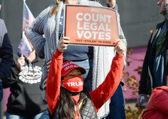 Donald Trump supporter Odessa Schmidt, 40, of Novi joins a rally at TCF Center in Detroit contesting the counting of absentee ballots.