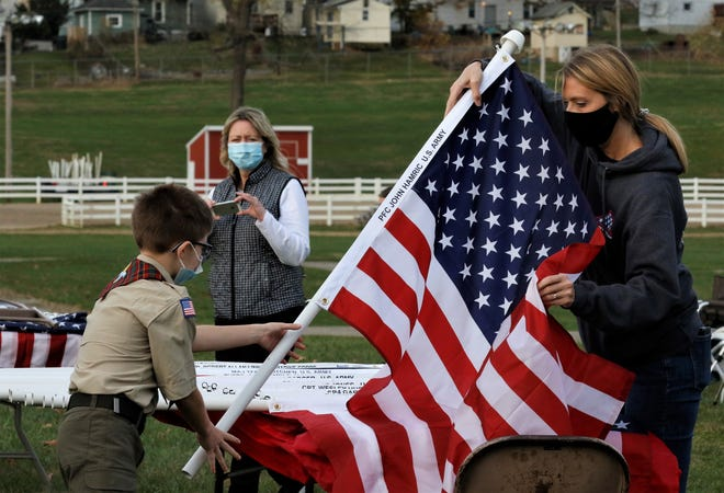 Evan Bartos, left, takes a flag to post in the Field of Heroes, part of the Freedom's Never Free, a celebration of military veterans and first responders, on Nov. 5.