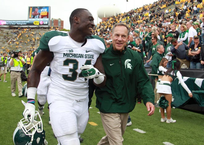 "Mark Dantonio walks off the field with linebacker Taiwan Jones after the Spartans' 26-14 victory at Iowa on Oct. 5, 2015. ""It was a game we pointed to and said, 'We've got to win this one,' "" Dantonio said."