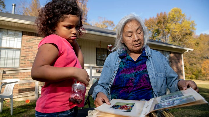 Lacie Bell looks through a photo album with her granddaughter, Emani, 4, on Thursday, Nov. 5, 2020, at the Choctaw reservation in Henning.
